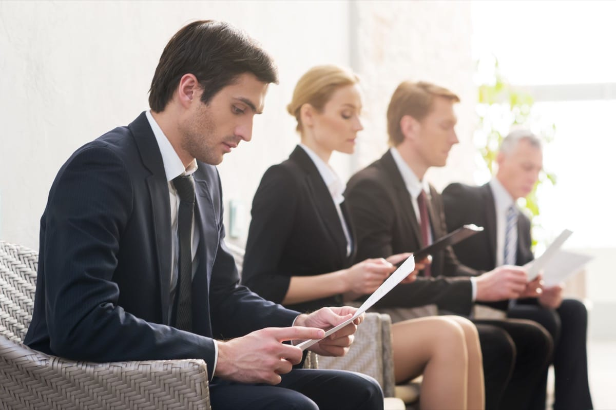 Job candidates. Four people in formalwear waiting in line while sitting at the chairs and holding papers in their hands, representing how to overcome talent shortages