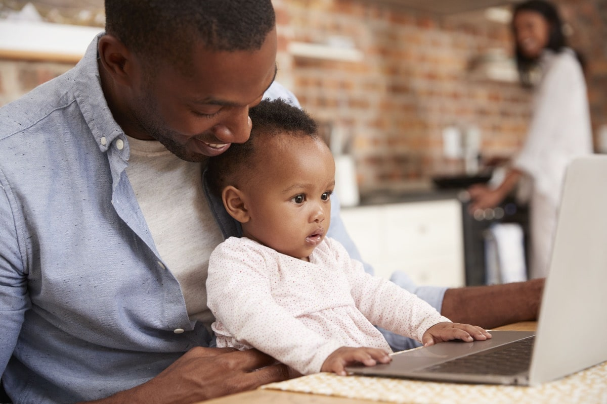 Father And Baby Daughter Use Laptop As Mother Prepares Meal; contingent workers concept