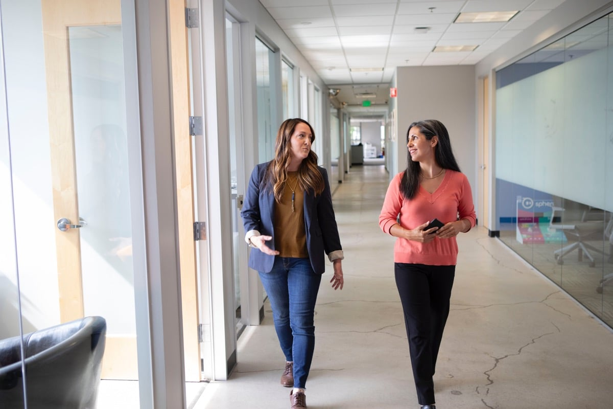two businesswomen meet while walking through a light-filled hallway; global talent intelligence concept