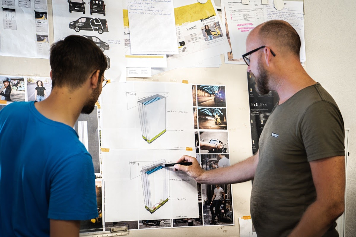 two engineers examine a diagram on a whiteboard; post-pandemic remote work concept