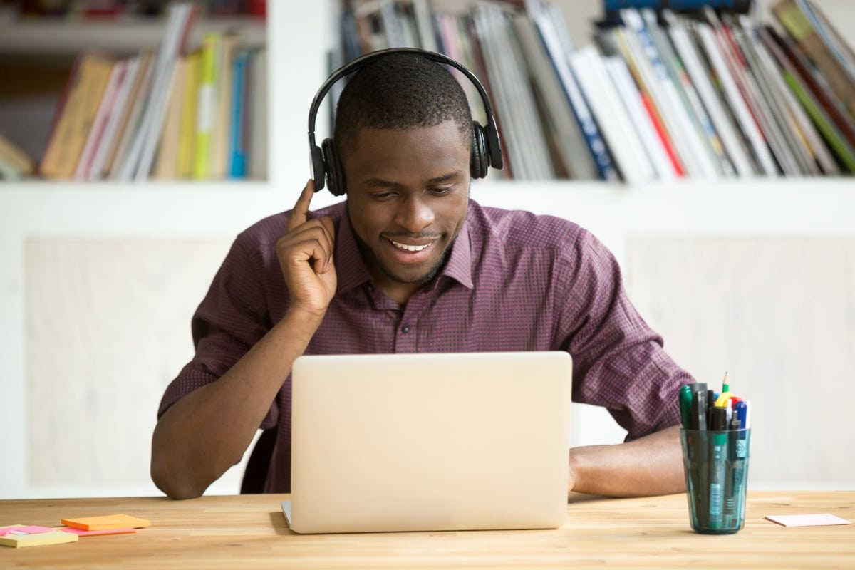 Smiling office worker in headphones looking at laptop screen; adapt your hiring concept