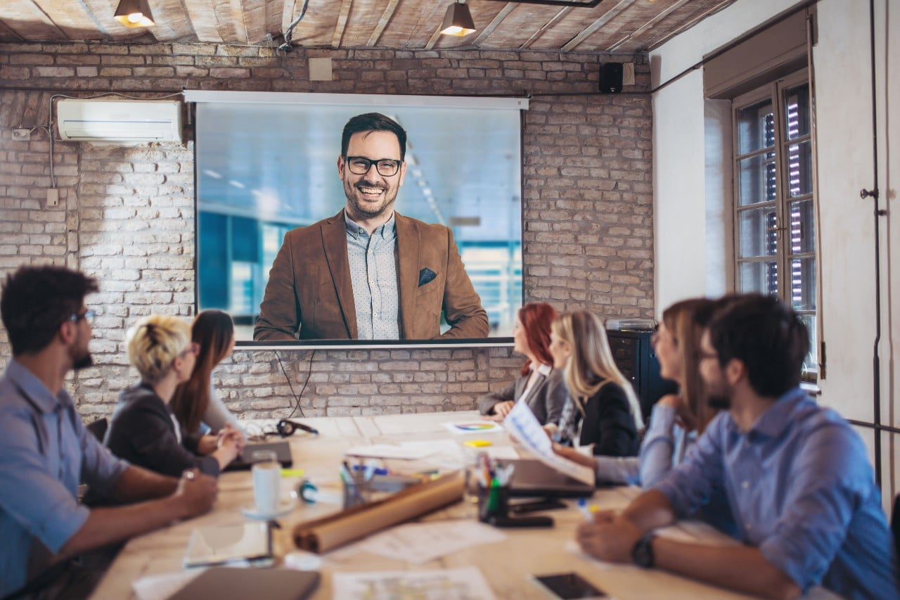 office workers in a conference room watch an onscreen presentation; concept: contingent talent tips